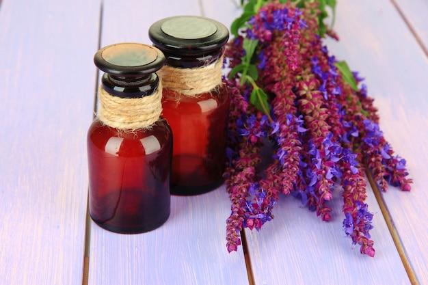 Flacons de médicaments et fleurs de salvia sur mur en bois violet