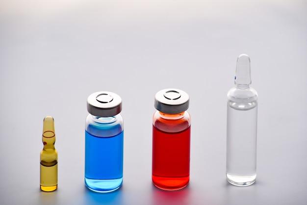 Flacons médicaux et ampoules pour injection. médicaments et traitement des maladies. flacons et ampoules bleus et rouges. pharmacologie et science. copiez l'espace.
