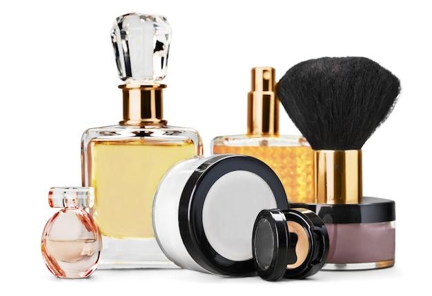 Flacons de parfum et cosmétiques avec pinceau isolé sur fond blanc