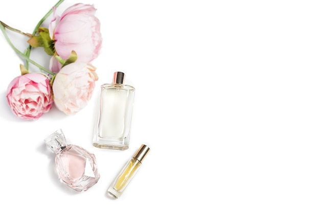Flacons de parfum avec des fleurs sur une surface claire. parfumerie, cosmétique, collection de parfums