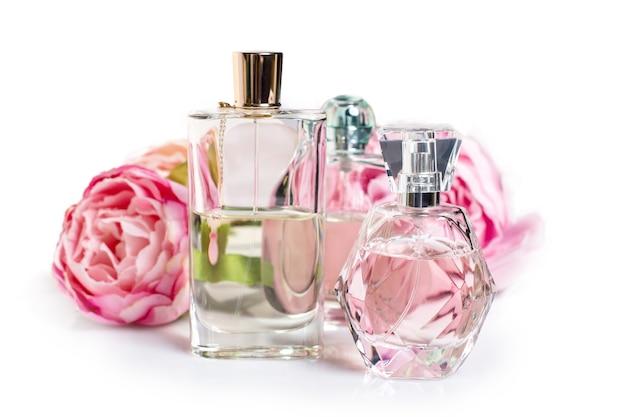 Flacons de parfum avec des fleurs sur une surface claire