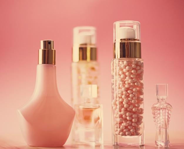 Flacons de parfum et gel de maquillage sur fond rose produits de beauté et cosmétiques de luxe effet vintage