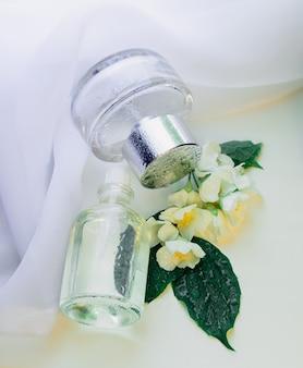 Flacons de parfum avec gouttes d'eau et fleurs de jasmin fond de tissu blanc avec essence florale