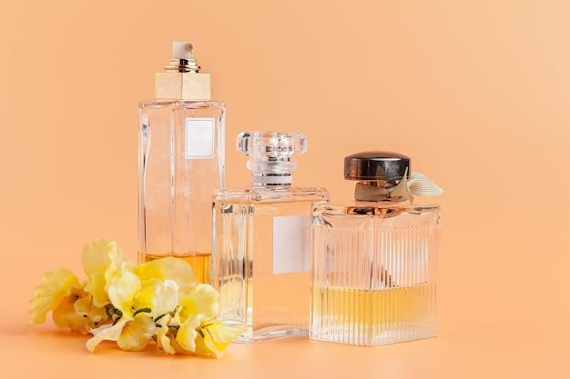 Flacons de parfum avec des pétales de fleurs sur beige