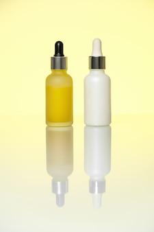 Flacons de sérum sur fond jaune clair. hydratant, vitamine c, acide hyaluronique.