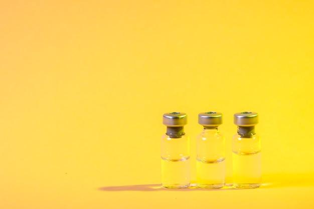 Flacons de vaccin sur surface jaune