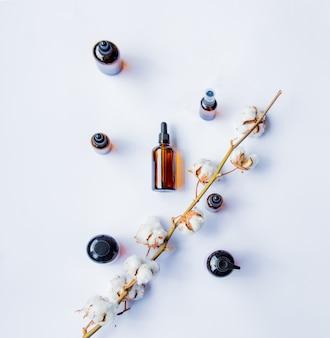 Flacons en verre de parfumeur avec des parfums et une branche de coton sur une surface blanche.