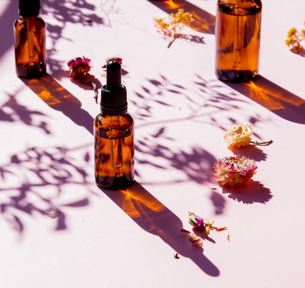 Flacons en verre de parfumeur avec des parfums et des fleurs sèches sur une surface rose.