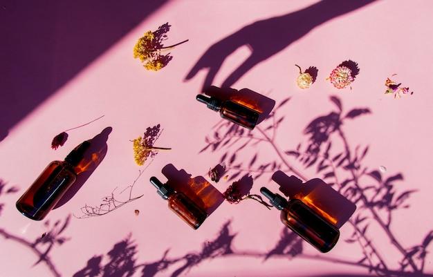 Flacons en verre de parfumeur avec des parfums et une main féminine sur une surface rose.