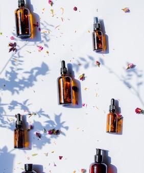 Flacons en verre de parfumeur avec des parfums sur une surface blanche.