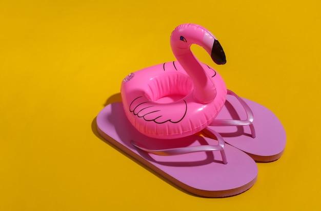 Flamant rose gonflable avec des tongs sur fond jaune ensoleillé. été, concept de vacances à la plage. minimalisme.