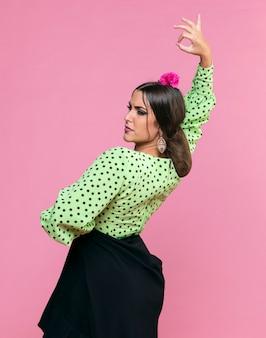 Flamenca femme dansant sur fond rose