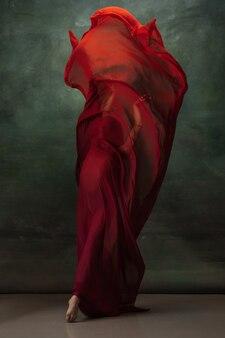 Flamme de feu. ballerine classique gracieuse dansant sur fond de studio sombre. tissu rouge foncé. le concept de grâce, d'artiste, de mouvement, d'action et de mouvement. semble en apesanteur, flexible. style de mode.