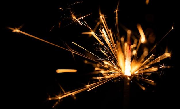 Flamme de sparklers, sur mur noir, mise au point sélective.