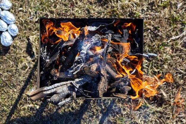 Flamme. vieux brasero en métal rouillé avec du bois et des charbons ardents