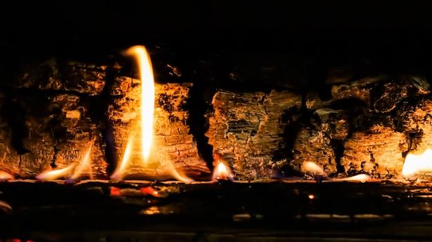 Flammes de feu et charbons ardents de bois brûlé dans la cheminée