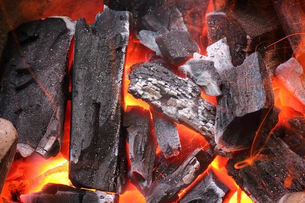 Flammes de feu avec des étincelles sur les charbons
