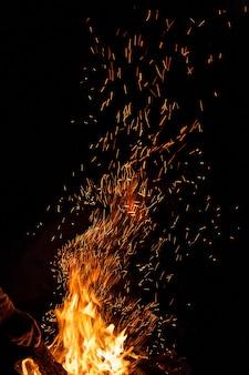 Flammes de feu avec des étincelles sur fond noir