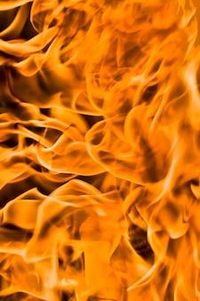 Flammes orange de bois et d'autres matériaux, gros plan, flou ou faible profondeur de champ
