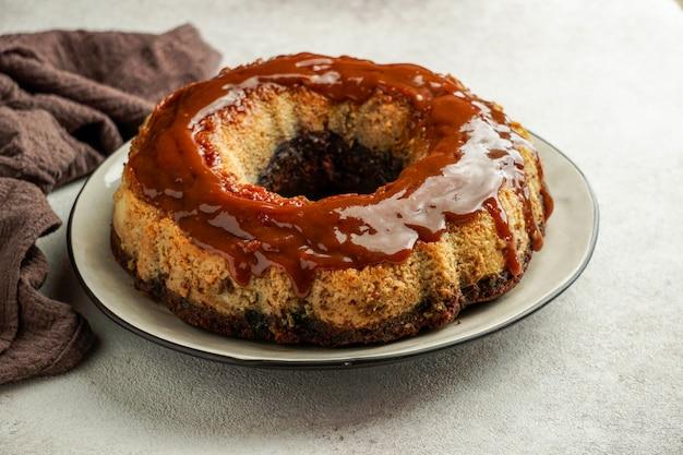 Flan au chocolat, chocoflan mexicain, gâteau au biscuit au chocolat et flan au caramel avec une sauce au caramel sur le dessus, sur une table en bois foncé