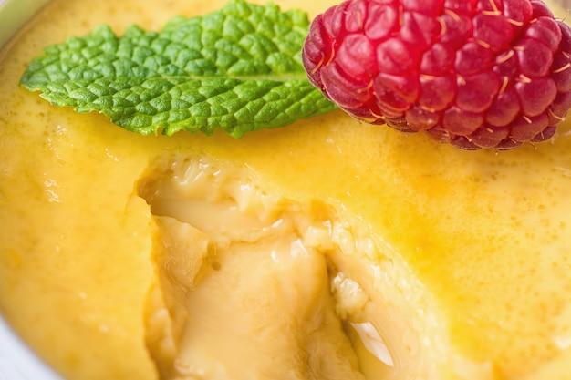 Flan de crème pâtissière aux œufs de vanille sucrée avec framboise fraîche et menthe dans une tasse à portion ramassée.