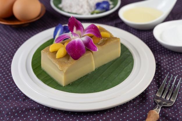 Flan sur une feuille de bananier dans un plat blanc avec des fleurs de pois et des orchidées