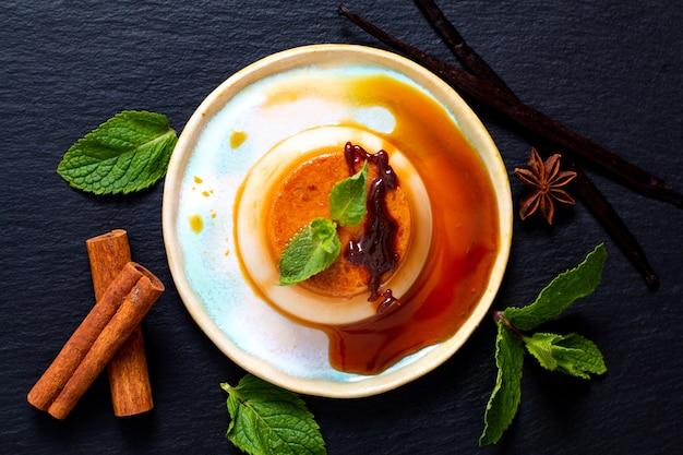 Flan vanille au caramel ou panna cotta avec des gousses de vanille et des épices sur un motif de pierre noire