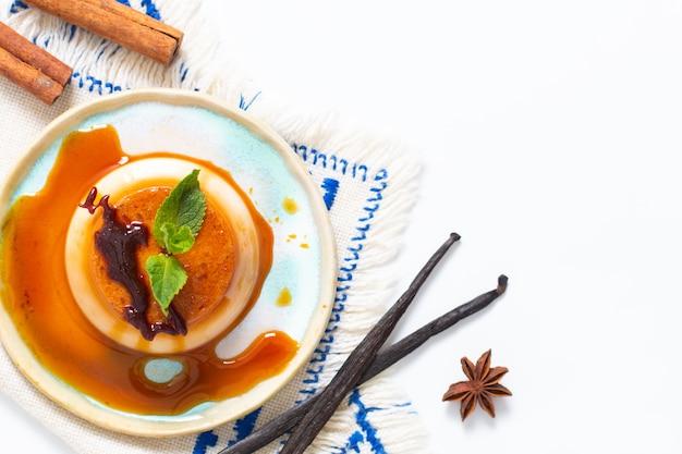 Flan à la vanille caramel ou panna cotta avec des gousses de vanille et des épices sur fond blanc