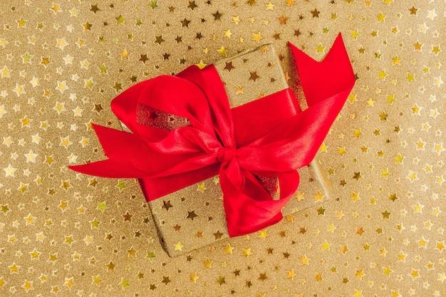Flat lay christmas ou party background avec boîte-cadeau en or avec noeud rouge sur or