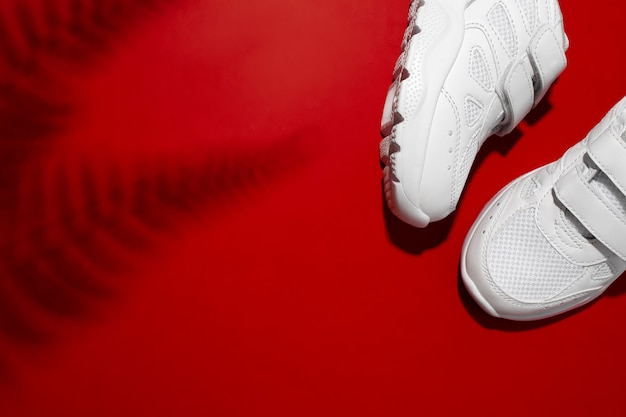Flat lay deux baskets unisexes blanches avec velcro avec des ombres de fougères ou de feuilles de palmier isolées sur un fond rouge...