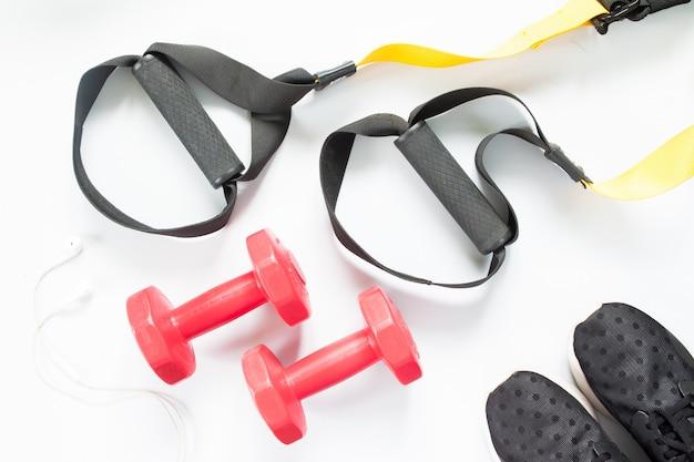Flat lay of écouteurs, baskets et équipement de sport sur fond blanc. vêtements de sport, vue de dessus