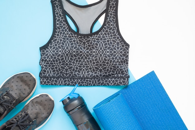 Flat lay of sport equipment with sport clothing in blue and black color theme