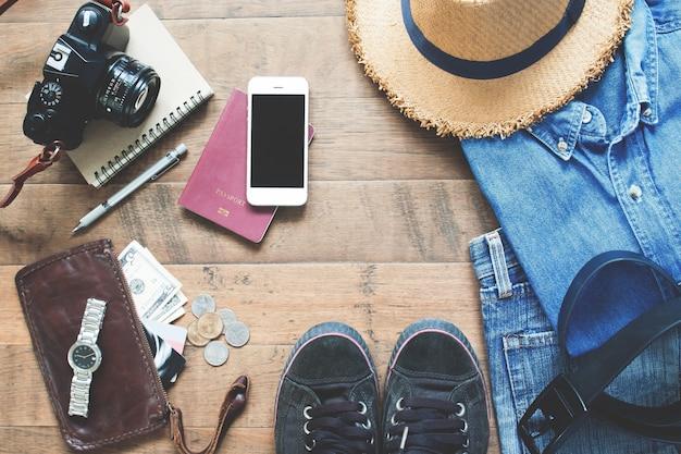 Flat lay of treveler's items, accessoires de vacances essentiels pour les jeunes voyageurs intelligents, concept de voyage sur fond en bois