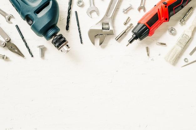 Flat lay d'outils de construction de travail sur bois blanc grunge.