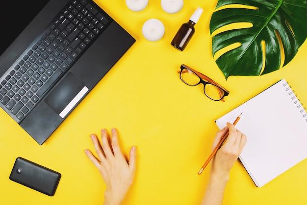 Flatlay d'affaires avec ordinateur portable, téléphone mobile, lunettes, feuille de philodendron, bougies, crème et mains de femme tenant un stylo.