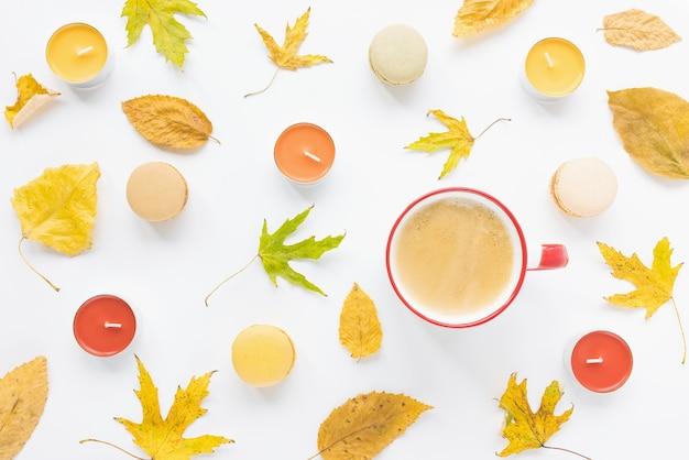 Flatlay automne feuilles jaunes bougies tasse de café et macarons sur fond blanc concept d'automne