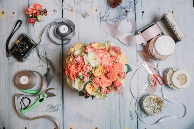 Flatlay de bouquet de mariage orange et des rubans sur la table de travail