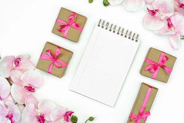 Flatlay de cadeau présente des boîtes avec ruban rose et fleurs d'orchidées sur fond blanc vue de dessus. carnet de notes ou écriture de journal intime.