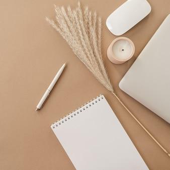 Flatlay de cahier à spirale avec feuille de papier vierge. ordinateur portable, herbe de la pampa, papeterie sur fond pastel beige pêche.