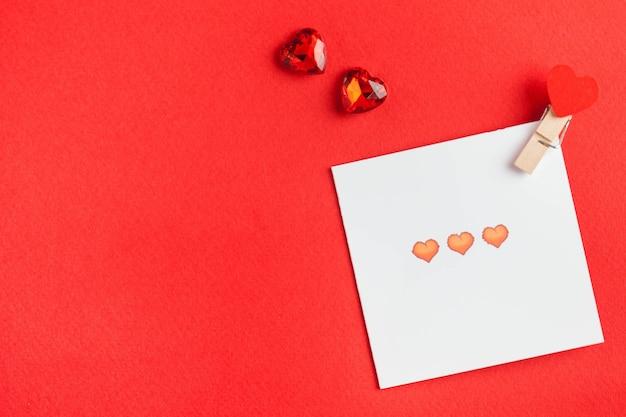 Flatlay coeurs rouges, carte d'amour sur une surface rouge