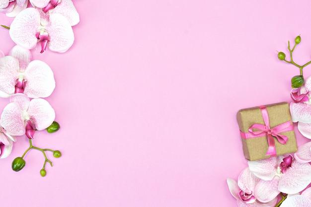 Flatlay de coffret cadeau unique présent avec ruban rose sur fond rose avec vue de dessus de fleurs d'orchidées