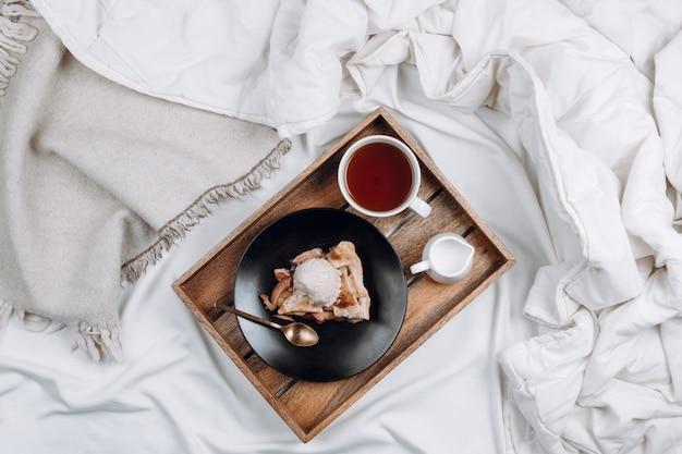 Flatlay confortable de lit avec plateau en bois avec tarte aux pommes végétalienne, crème glacée et thé noir sur des draps blancs et des couvertures