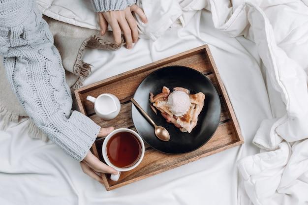 Flatlay confortable de lit avec plateau en bois avec tarte, crème glacée et thé noir et mains de femme en pull gris tenant la tasse