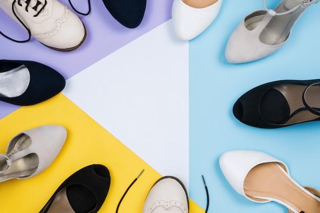 Flatlay élégant avec diverses chaussures à la mode féminines: chaussures brogues, appartements, chaussures à talons hauts sur fond bleu, violet, blanc et jaune. copyspace