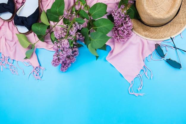 Flatlay d'été avec foulard rose, chapeau de paille et sungasses sur bleu