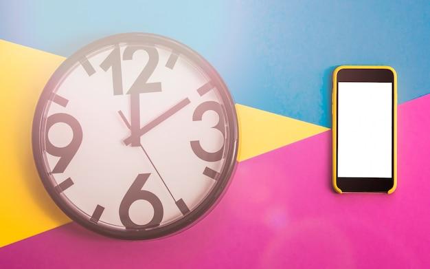 Flatlay avec horloge et clavier sur trois tons de couleur unie jaune, violet et bleu clair