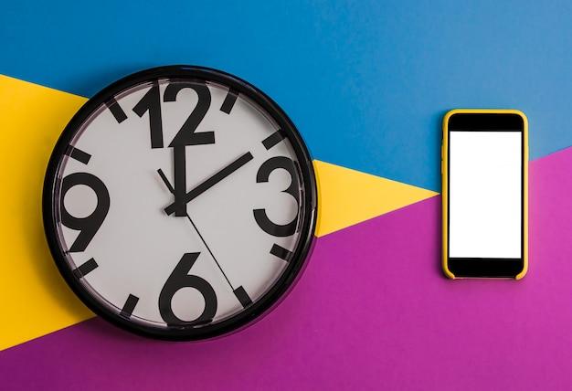 Flatlay avec horloge, smartphone sur bac de couleur unie trois tons jaune, violet et bleu clair