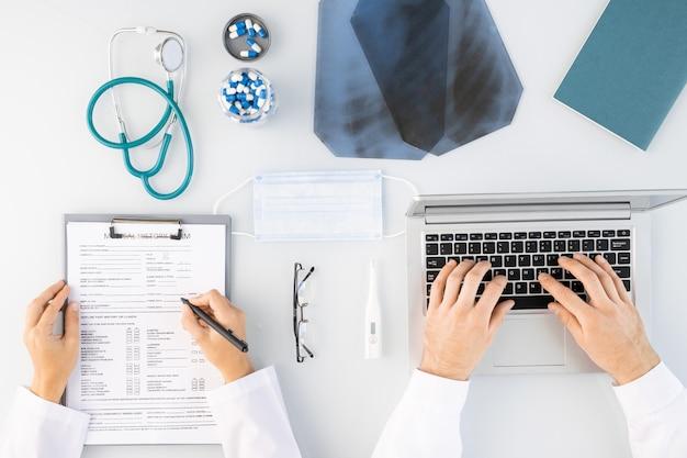 Flatlay des mains de cliniciens masculins et féminins prenant des notes médicales et tapant par ordinateur portable entouré d'images radiographiques, de pilules et d'un stéthoscope