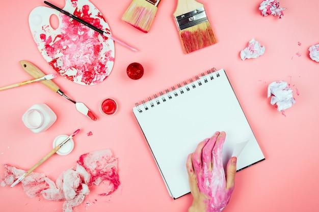 Flatlay avec des mains de femme couvertes de peinture, pinceaux, carnet de croquis et palette et autres fournitures d'artiste, concept de créativité