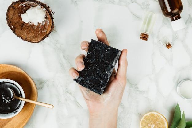 Flatlay des mains de femme tenant du savon au charbon de bois fait maison avec ses ingrédients sur le côté, concept de beauté à la maison naturelle